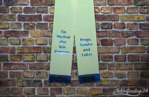 Trauerschleife in Maigrün mit blauem Text vor gemauerter Wand