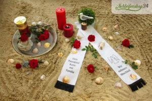 weiße Trauerschleife liegt mit Muscheln im Sand