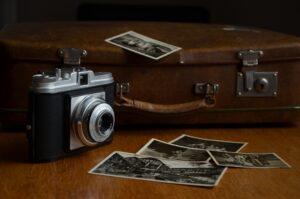 antiquarische Kamera vor einem alten Koffer mit teilweise vergilbten Aufnahmen