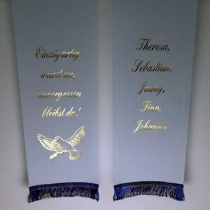 Schleife in hellblau mit glänzend-goldenem Text und blauen Fransen